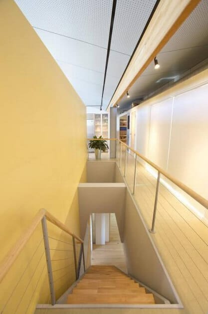 Straight staircase with light wood treads and steel railing topped with wooden handrail against a yellow wall.