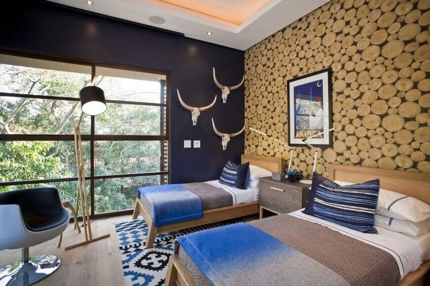 This western themed bedroom features a log accent wall, which draws in the eye and gives the space a unique touch. The beds are separated by a wooden bedside table, and they sit upon a patterned area rug that agrees with the theme of the room.