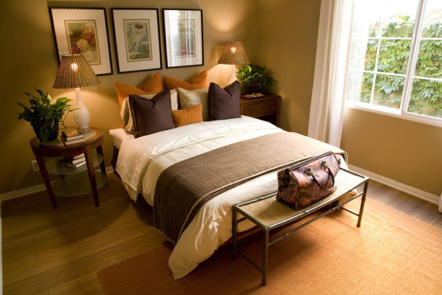 Again utilizing decorative pillows in place of a headboard, this brown and orange bedroom makes a stunning color combination against the beige and tan backdrop of the room.