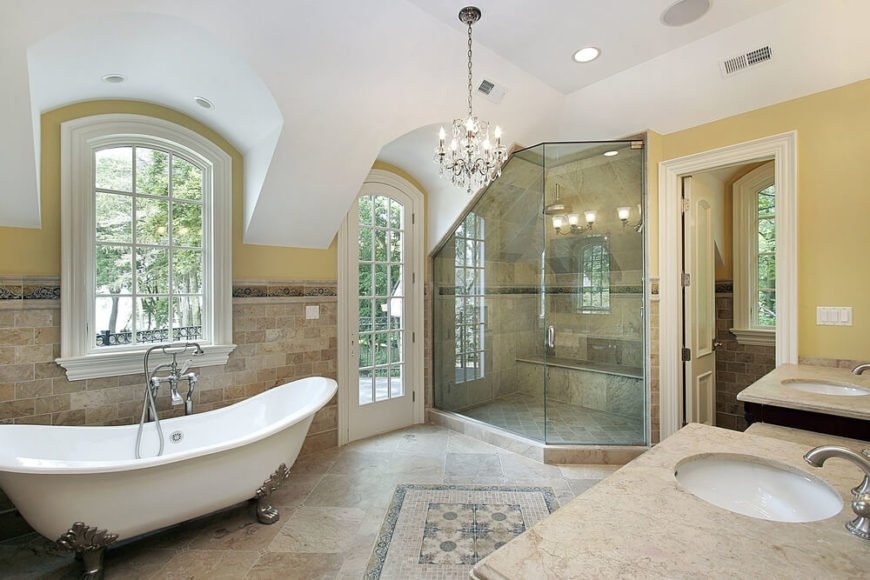 This spacious bathroom features a large corner shower, with a unique angled ceiling. The time on the floor runs halfway up the wall around the whole room, and the clawfoot tubs has its own space beneath a twelve pane window.