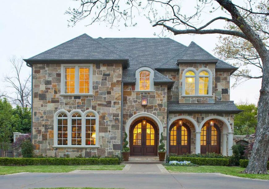 Not to be outdone, quarries created a method of making thin sheets of stone. This made stone easier to carry and install, thus making it a bit more affordable. This multi-colored stone house makes a striking show with its puzzle-piece like exterior.
