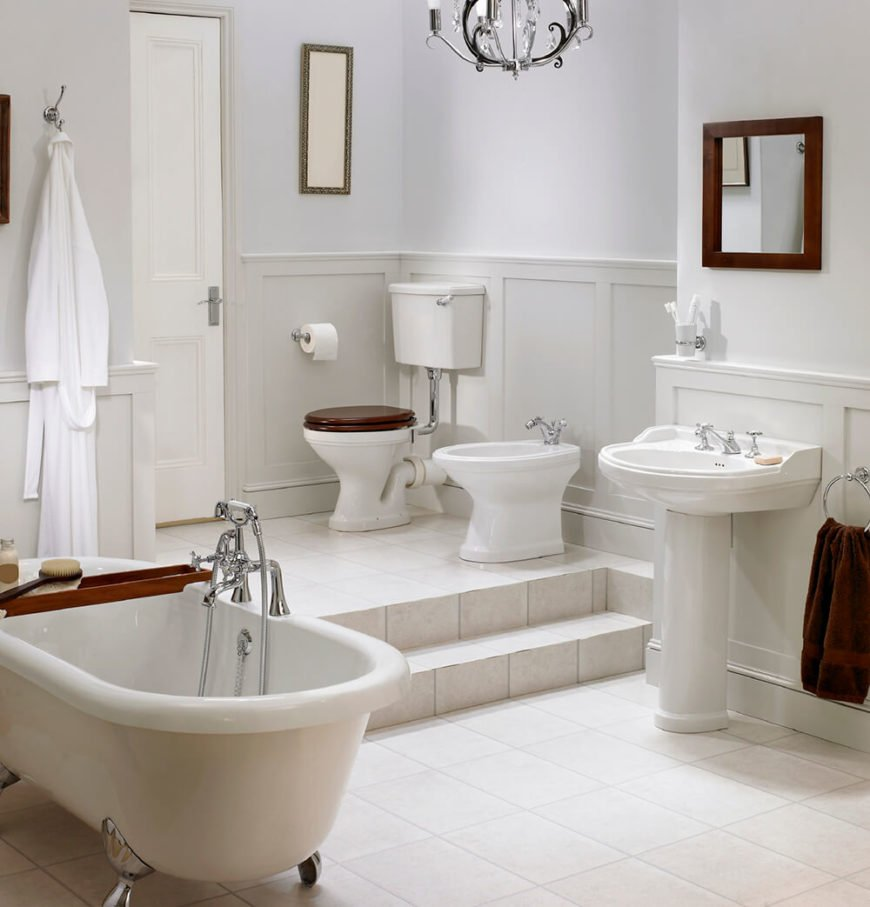 This bathroom features two different levels, the upper featuring a toilet and bidet, and the lower featuring the clawfoot tub and pedestal sink. The whole room is saturated with white, with touches of rich brown color for an accent.