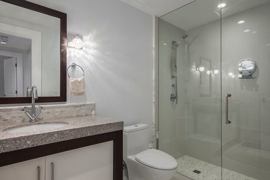 The bathroom has a soft neutral gray on the walls. The countertops are made of a sleek granite and chocolate hardwood accents.
