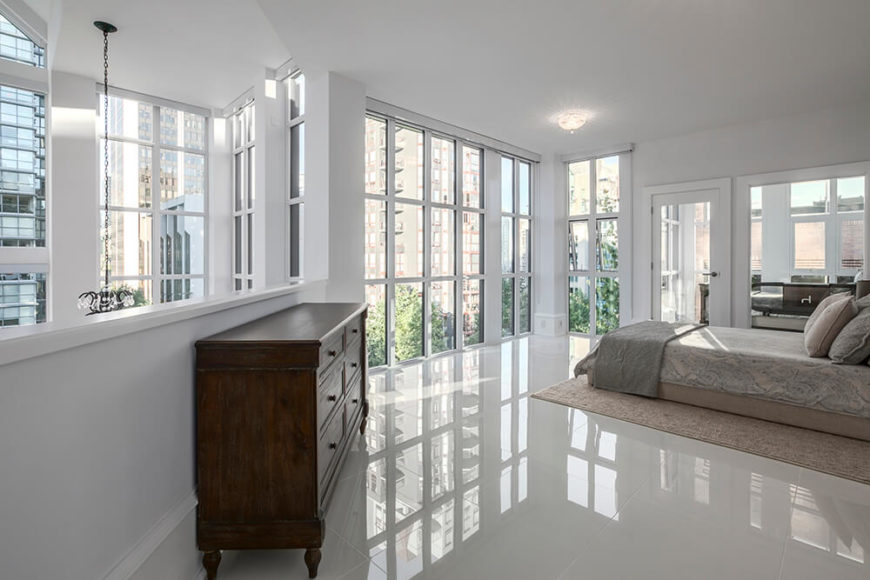 The primary bedroom is on the second floor of the home, and can see down into the office space from the balcony area. Because of the half wall, the primary bedroom gets twice as many windows as other bedrooms in the house.