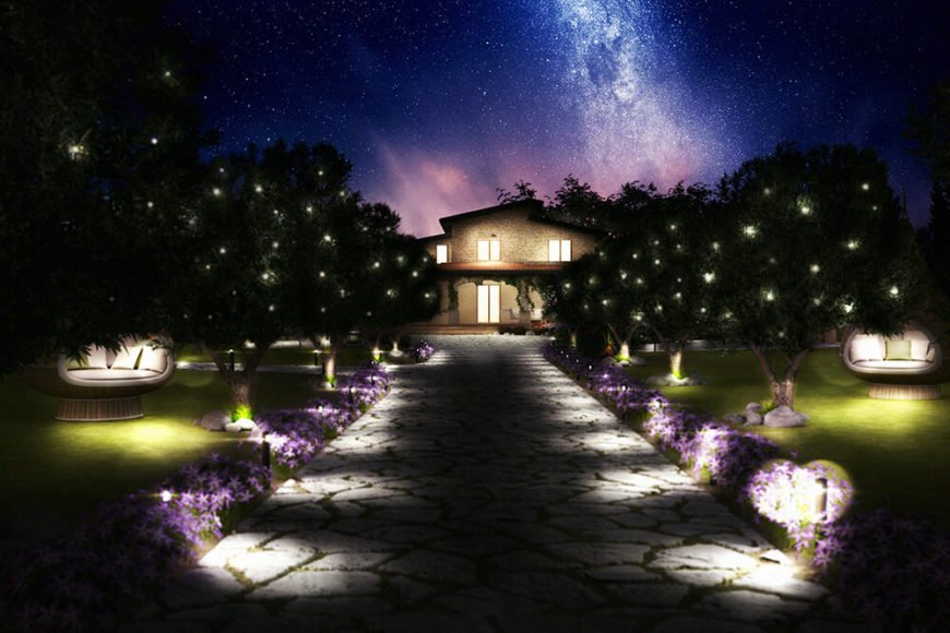 The subtle lights hidden amidst the garden frame the craggy stone path approaching the home. In the distance, we see the large windows glowing around the stone facade.
