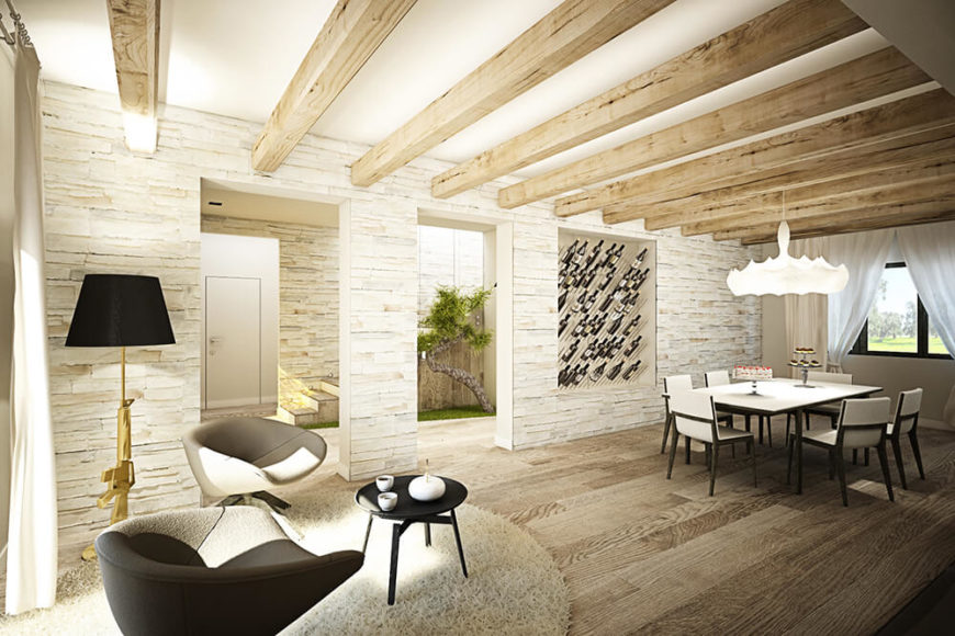 Stone walls stand between the rich hardwood flooring and exposed natural wood ceiling beams above. The transparent wine rack built into the wall makes for convenient access to the dining area.