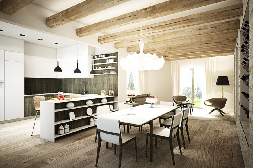 Next to the black and white dining table, we see the kitchen sporting a matching high contrast palette. The countertop straddles a set of open shelving, while offering a space for in-kitchen dining.