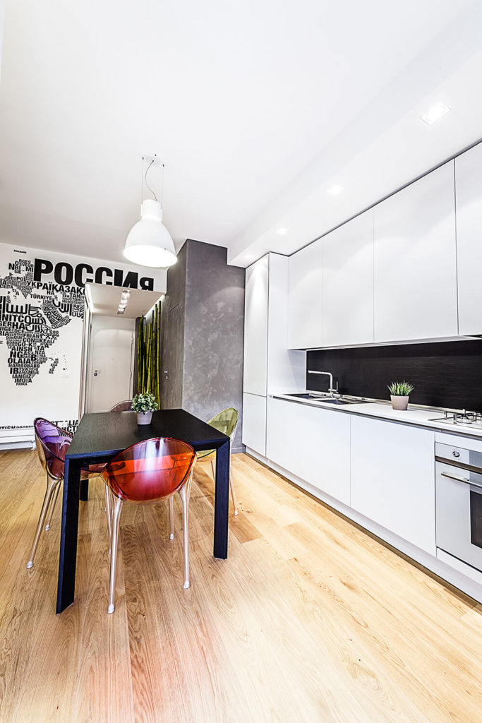 With the dining table floating in the open plan space, the kitchen is a loose, inviting corner of the home. Stainless steel appliances match the ultra-modern tone of the cupboards.
