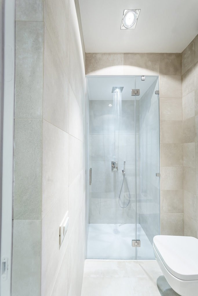 The walk-in, glass enclosed shower features an ultra-modern rainfall shower head, and is illuminated by a strategically aimed recessed light in the ceiling.
