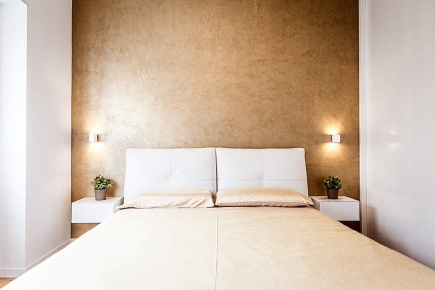 In the primary bedroom, we see the gold accent wall backing the light hued bed, flanked by a pair of floating bedside tables in white. Bespoke wall sconces glow sympathetically beside the white pillow headboard.