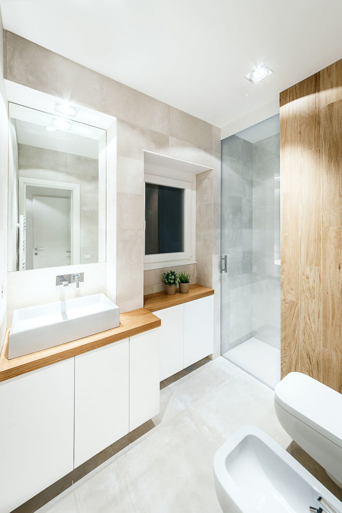 The primary bath sports a similar mixture of glossy whites, light grey concrete, and rich natural wood. The vanity once again boasts a rectangular vessel sink over hardwood countertop.