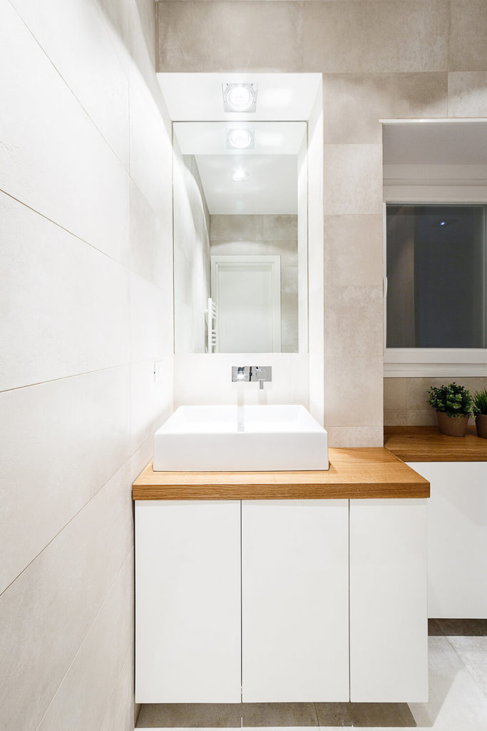 The sleek white cabinetry panels are hardware-less for an immaculate, minimalist look. The sink features very modern wall-mounted plumbing.