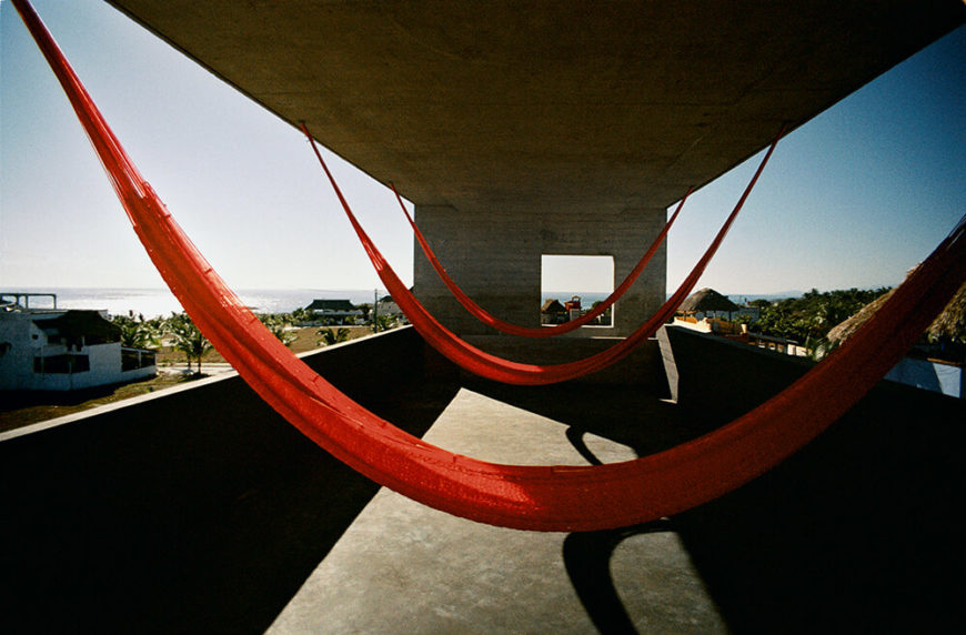 The upper deck, in the vertical cantilever, makes for a great place to sit and relax while enjoying a warm breeze and taking in the view. Bright red hammocks carry the color throughout the house.