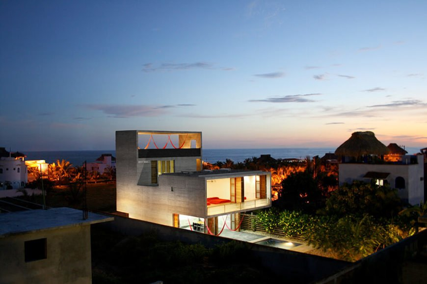 Near the ocean, the house at night is quite a sight to see. The unique shape and structure is both similar to the surrounding houses and vastly different in its modern design.
