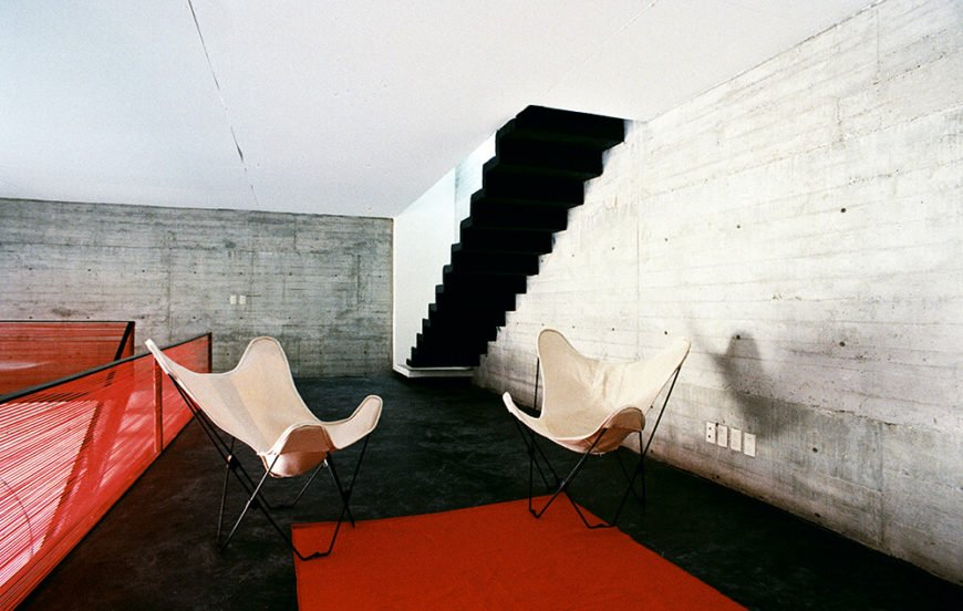 The second floor houses a small, comfortable siting area with floating stairs leading up to the sleeping area and upper deck. The walkway against the far wall leads to two bedrooms at the front of the cantilever. The raw concrete walls add a subtle pattern and texture to the walls.