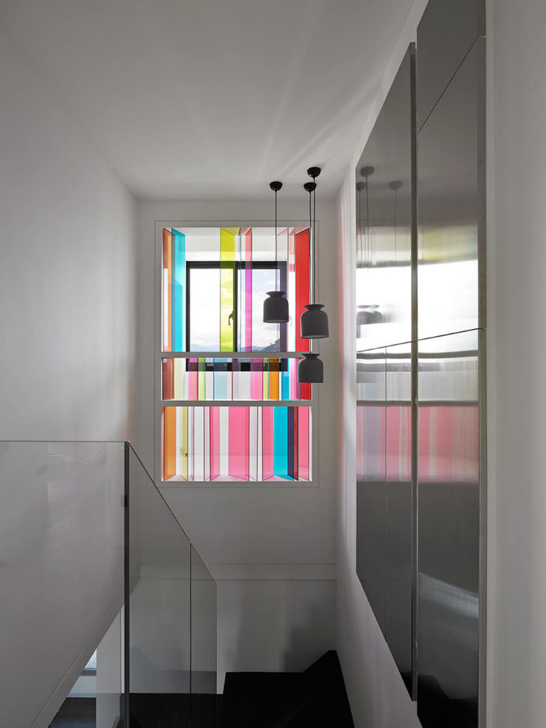 The other side of the stair takes advantage of the large window and brings a riot of bright color into the space. The play of light through the colored glass creates beautiful colors along the otherwise plain walls.