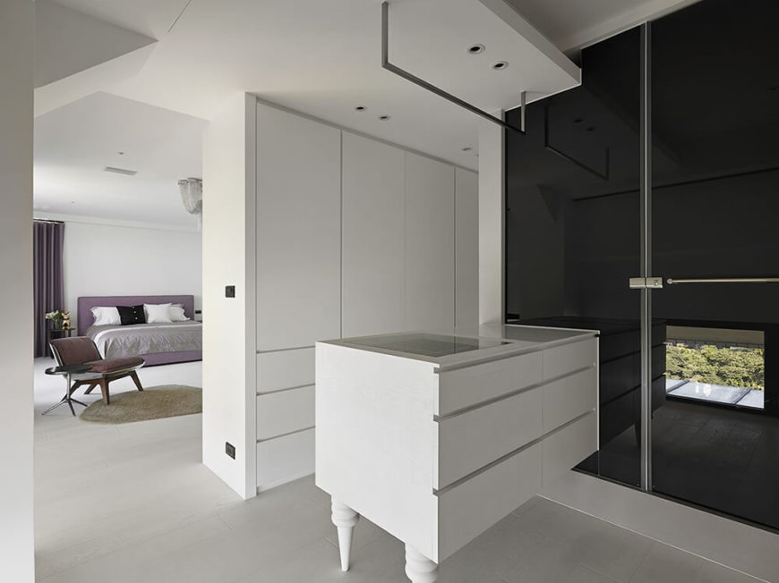 In the ensuite primary bathroom and walk-in closet, this customized cabinet is used to store accessories and create a space to get ready while the stainless steel bar is meant to be a place to hang outfits to be worn.