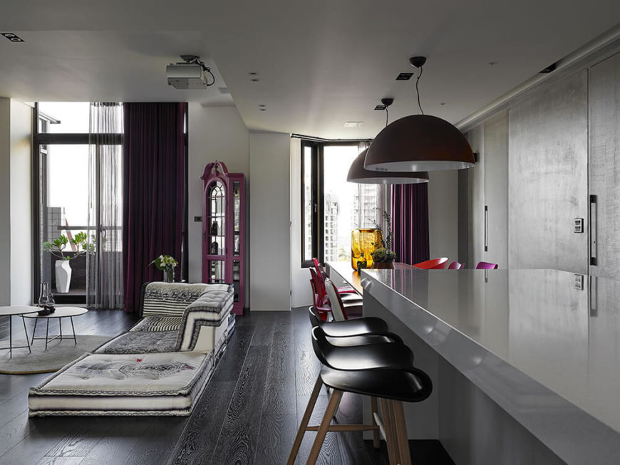 Beyond the unique sofa is a purple cabinet from the owner's childhood. Originally teak, the designers were given permission to paint it and it now holds a collection of item sentimental to the owners. The choice to paint it was made to better include it in the overall design of the space. A small balcony can be seen through the sliding door behind thick purple curtains.