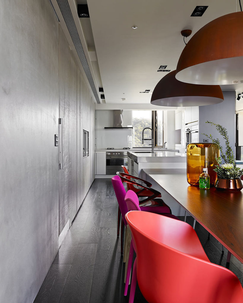It was very important to the owners of the house that the kitchen and dining area be able to accommodate guests and visiting family. Here you can see a few of the bright chairs used to bring color into the space. Further along you can see into the sleek kitchen space.