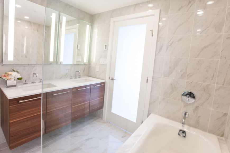 In the primary bathroom, we see a broad double vanity through the glass bath enclosure. The door features smoked glass to allow for both privacy and natural light.