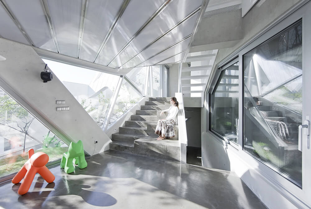The interior of the home sparkles with stainless steel and glass throughout. The interconnected levels of the home are visible, courtesy of the open design.