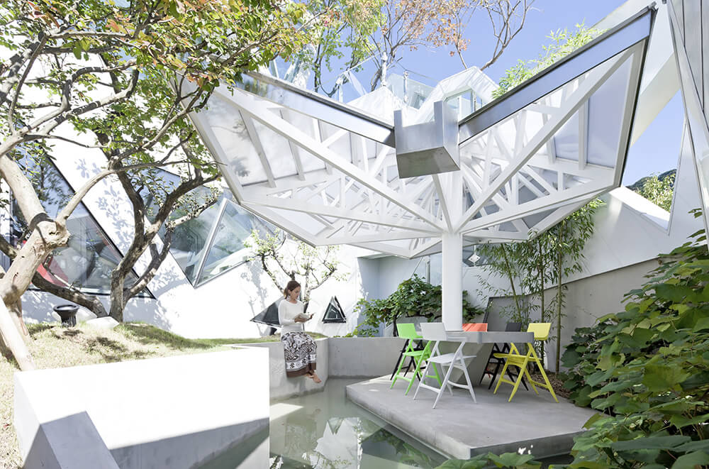 Here's another level to the living roof, a spectacular inner courtyard with a water feature, shading, and a built-in picnic area. Lush greenery mixes with clean concrete lines beneath an expanse of shaded glass.