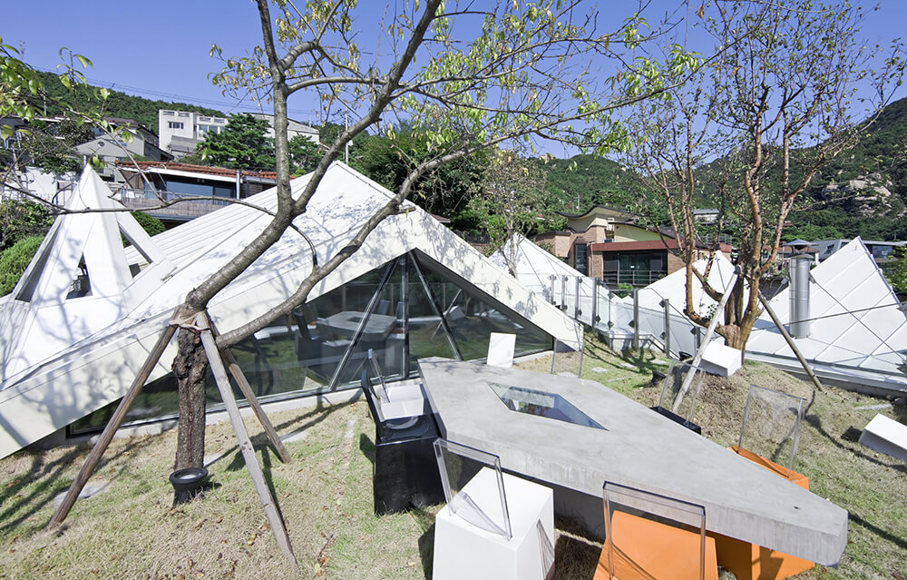 Moving onto the rooftop, we get a close look at the expansive interlocking garden, full of fruit trees. The angular shapes of the home surrounding this area spike it with high contrast and detail.