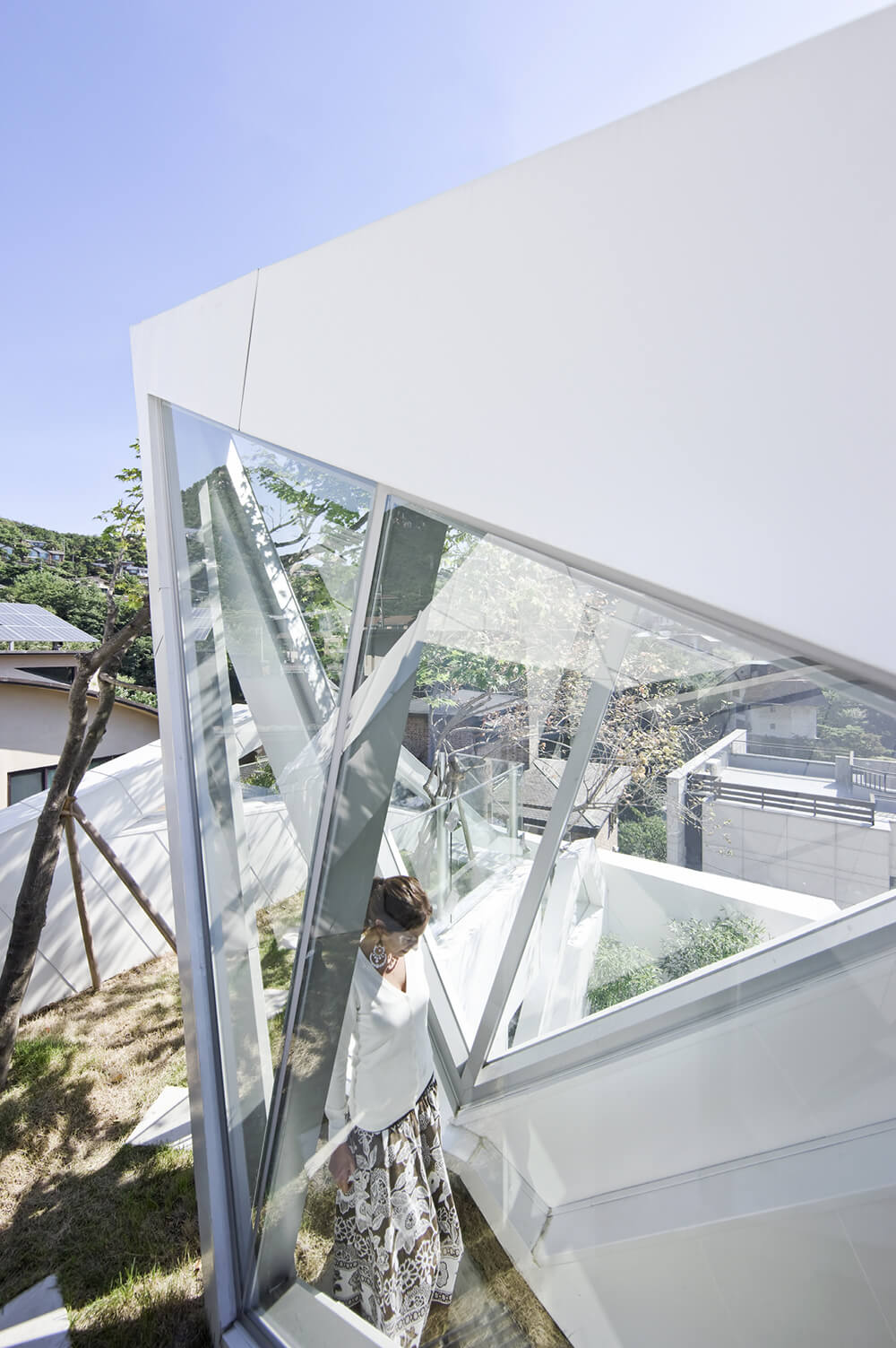As we see one of the homeowners enjoying the lush greenery in her rooftop garden, the interlocking expanses of glass and sleek white space give way to the landscape beyond.