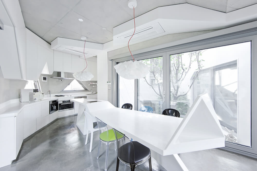 The kitchen is an immaculate white space, with sleek countertops and a lengthy island that turns into a dining table. Even the cabinetry and island reflect the angular, polygonal shape of the home itself.