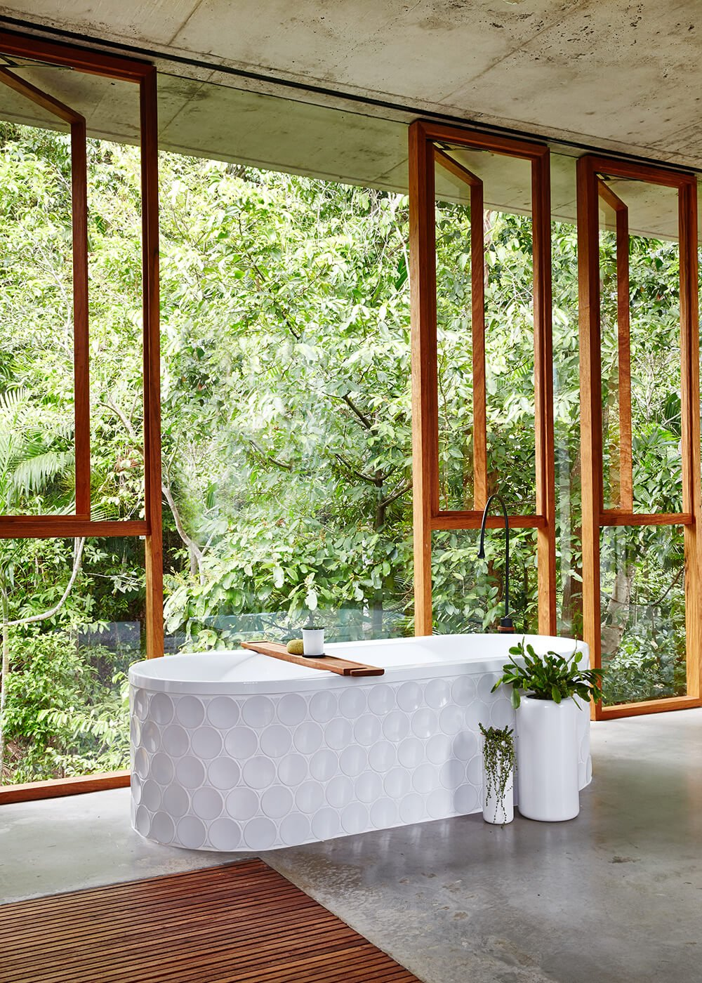In the primary bath, we see a large soaking tub with the same circular texture as the shower wall. Basking in the glow of sunlight and rainforest views, this is one of the most relaxing bathrooms we've ever seen.