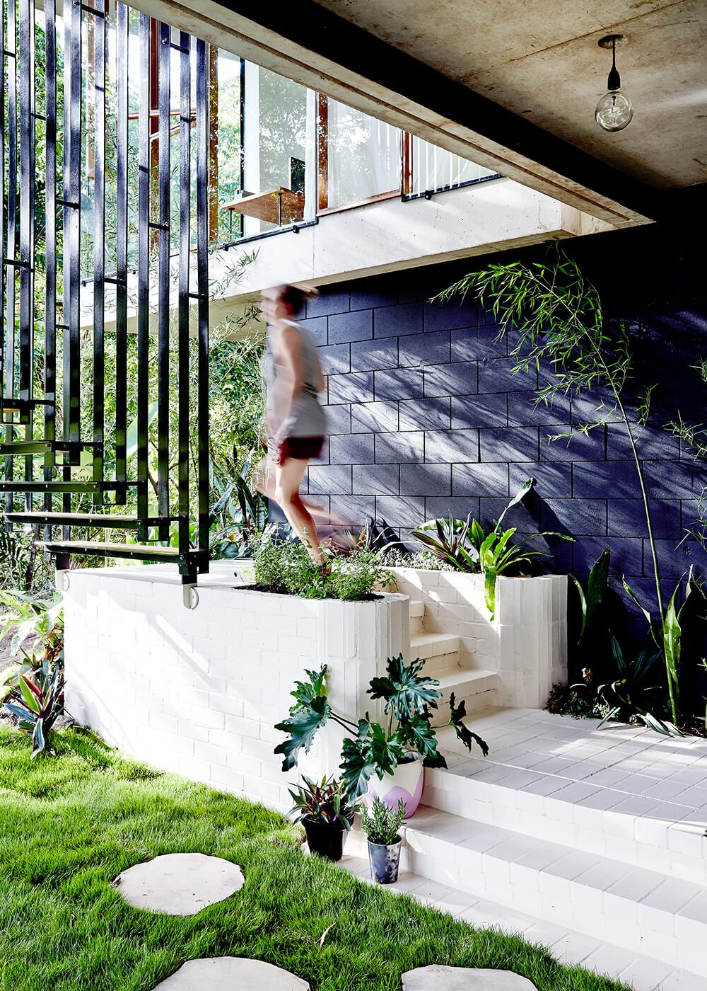 Moving down the outdoor staircase to the ground level, we come to the bold contrast where the dark brick foundation meets a white brick patio. This courtyard continues the structure's communion with nature.