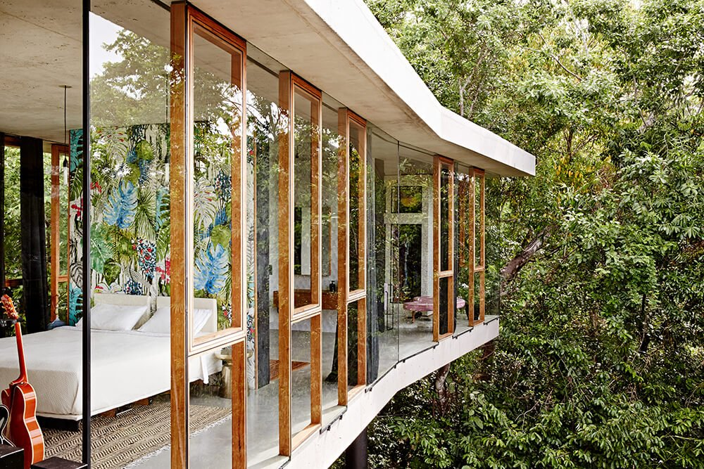 From the balcony outcropping on the upper level, we can see into the private wing of the home, with bedrooms and bathrooms wrapped in glass and natural wood.