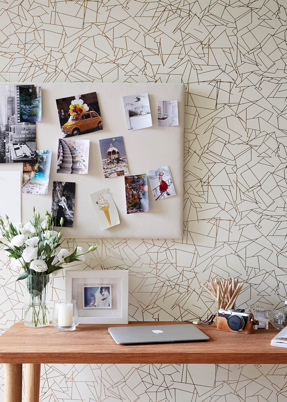 In a home office space, we see a natural wood writing desk standing against another textural feature wall.