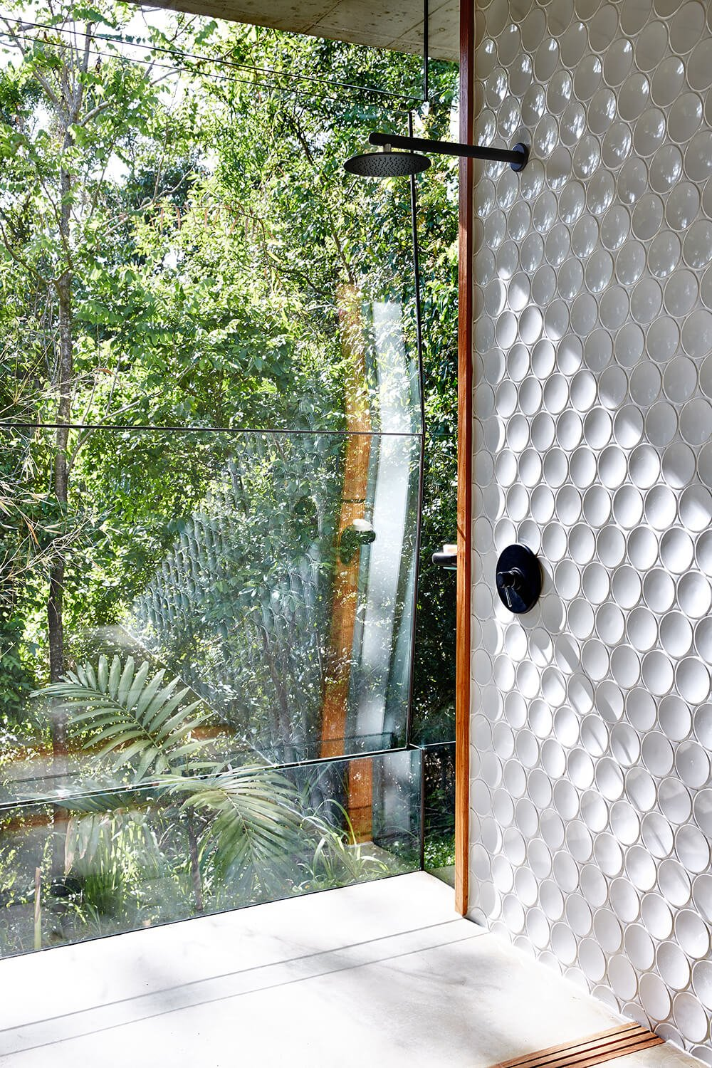 In this second bathroom, we see a similar open design shower next to the windows overlooking the rainforest. The glass panels here are louvered for myriad opening possibilities.