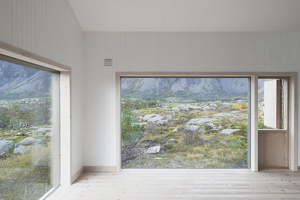 Inside the home, we can see out over the surrounding countryside via massive windows. The Dutch door at right serves the same purpose it originally had, allowing in light and air while filtering out low-level dust that swirls over the dry landscape.