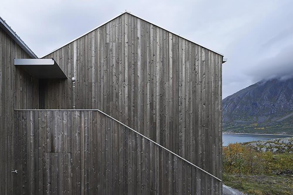 The rich wood paneling of the exterior meets steel and aluminum, perfect bedfellows in protecting the interior from the harsh northerly climate. Beyond the home, we can see the Norwegian Sea and nearby mountains.