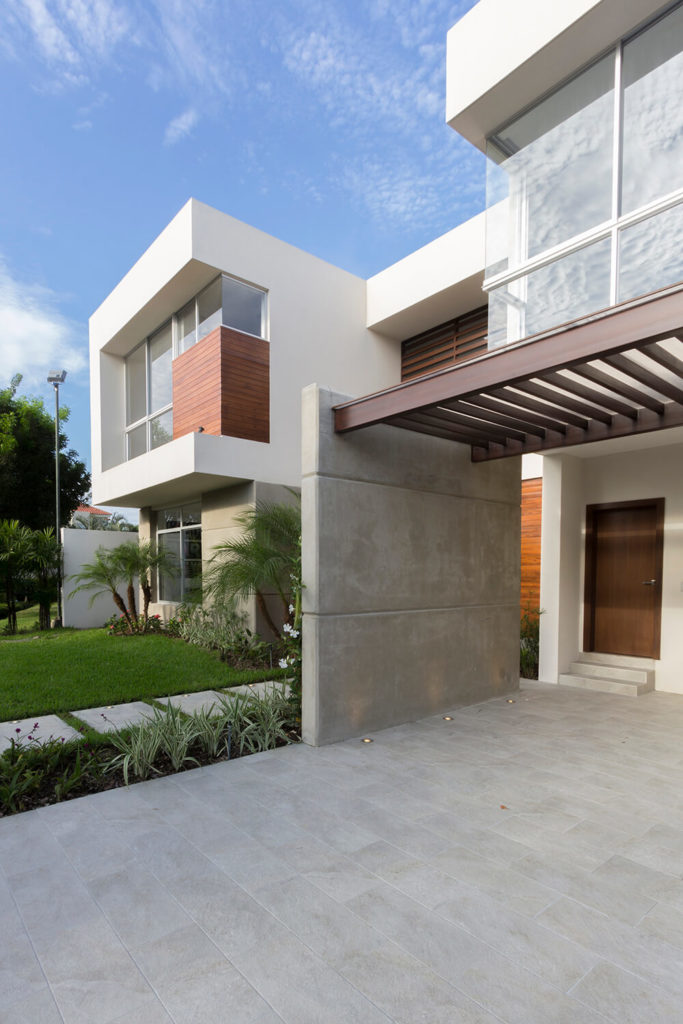The covered brick driveway balances the shape of the house and utilizes both wood and concrete. Small lights, like the ones in the walkway, are imbedded in the drive along the base of the concrete wall.