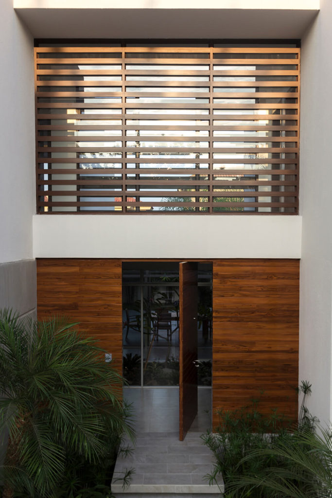 Here you can see the unique, pivot door installed for the front door. The second floor rooms are all connected by the glass and wood screened hallway seen here.