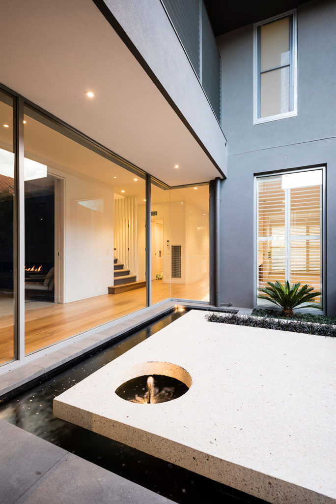 The concrete slab features another circular cutout with a water feature for ambiance. Marble chips, the signature feature in terrazzo concrete, create a beautiful finish on the polished surface of the slab. The boarder of the pond can better be seen here dividing the courtyard from the house.