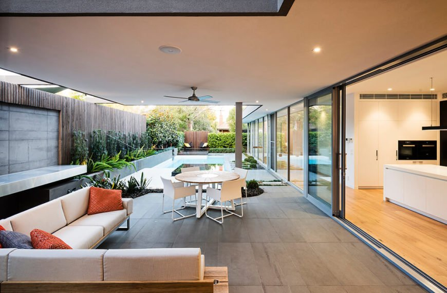 The seating area is covered by a roof supported by posts and opens up into the kitchen of the house by way of a large sliding door. The charcoal planter along the left side extends the entire length of the property and is filled with a carefully chosen selection of plants with a ficus hedge. The plants are backed by horizontal screen boards along the boundary of the property, creating a striking contrast.