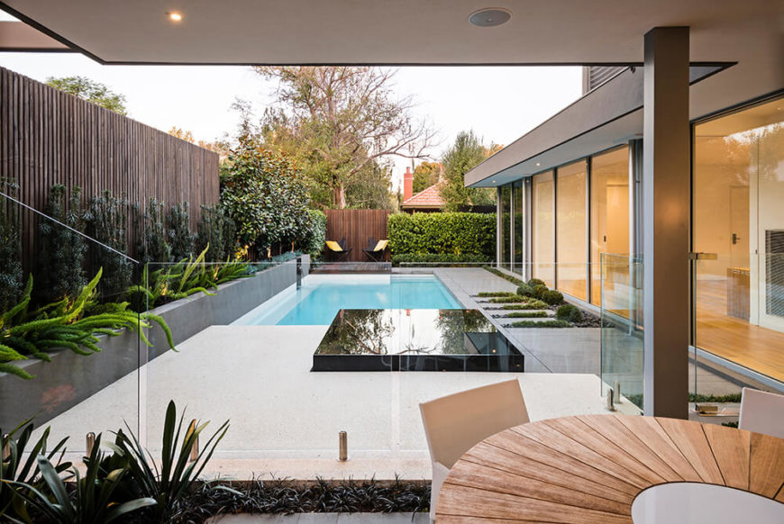 A bed of cliveas lines the edge of another polished concrete slab, serving as a sun deck, that borders the pool. Large windows border the entire backyard. The patio running along the pool is broken up similarly to the front yard with its bluestone stepping stones.