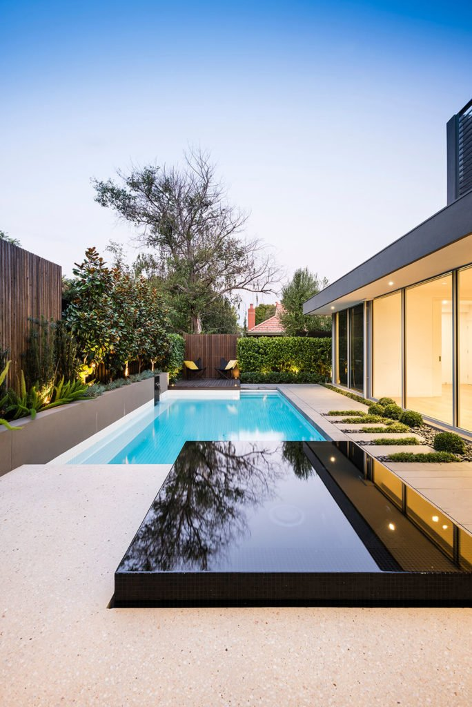 The alpine white contrasts nicely against the wet edge spa finished in black glass mosaic tiles that rises up from the white ceramic tiled pool. The sleek edges of the black matches the contemporary, minimal design of the exterior of the house.