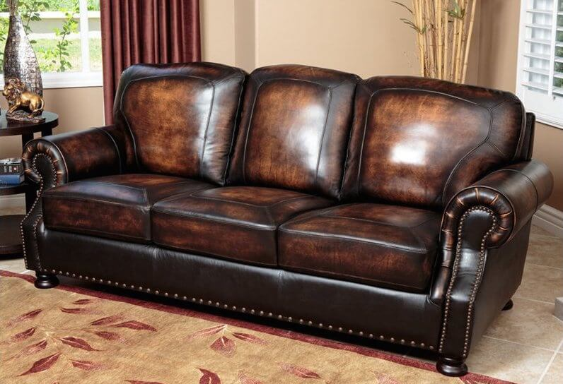 The rich burnt tone of this luxurious leather sofa enhances the sense of traditional charm. Roll arms and base feature nailhead trim, while the carefully detailed cushions infuse a sense of precision.