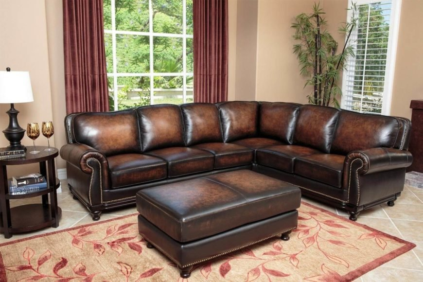 Here's an immaculately elegant dark leather sectional that will raise the luxury quotient of any man cave you place it in. Rich cushioning is bracketed by roll arms and bright nailhead trim, while the ottoman completes the utilitarian set.