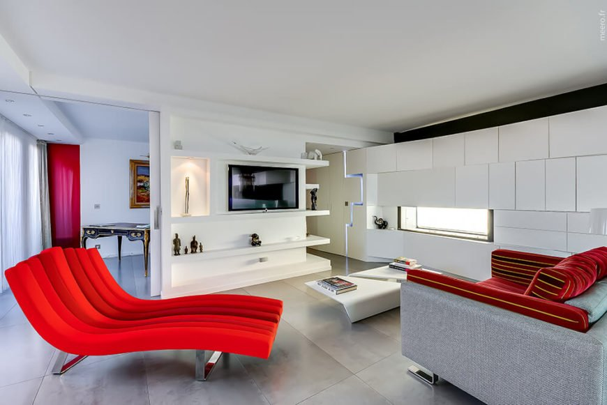 The living room is the best example for fierce and loud hues of red. This modern room is draped in mostly white, with seamless cabinets and shelves– but it has a surprise burst of red in the furniture.