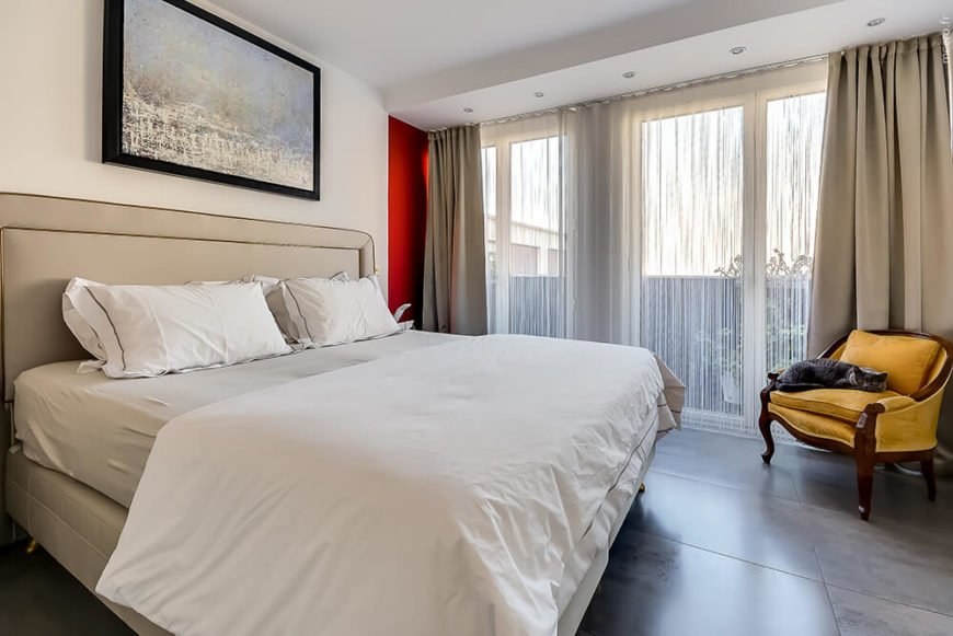 The primary bedroom is more subtle than the rest of the house for a calming and tranquil atmosphere. A soft canary yellow chair brings some color as well as the doorway to the bedroom.