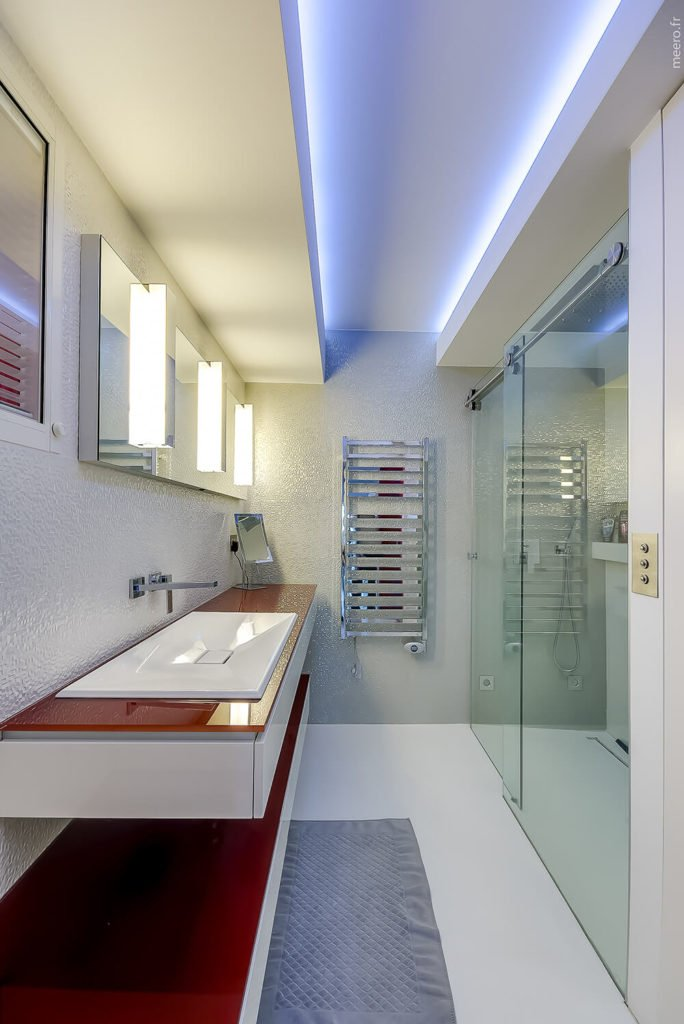 The bathroom continues the boldly fierce patterns of colors. A massive walk in shower is accented by soft blue lights in the ceiling. The floating counter tops are topped with a red gloss, and the floors are a flawless shimmering white.