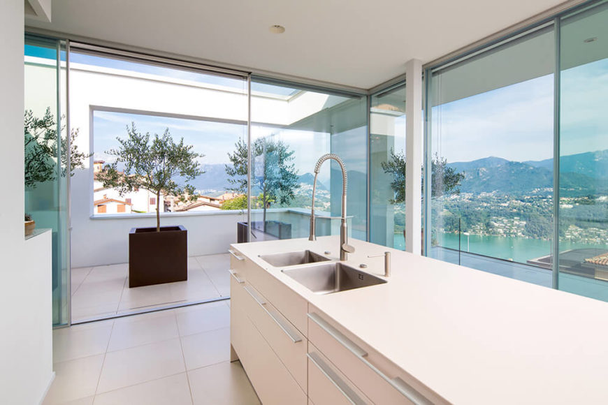 The kitchen centers on this sleek white island with built-in sink and storage possibilities. The wraparound glazing means that the expansive mountain views are afforded from inside the home.