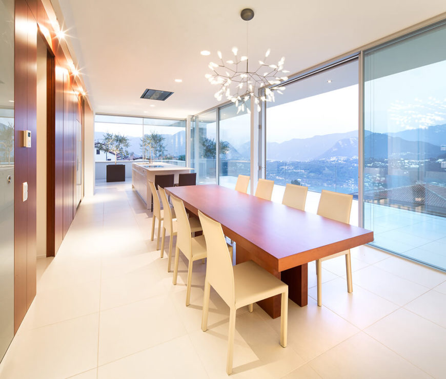 The grand open space design means that the kitchen shares a floor plan with the dining and living room areas. The rich wood dining table, along with matching wood paneling at left, offers a warm counterpoint to the white tile flooring and expanses of glass.