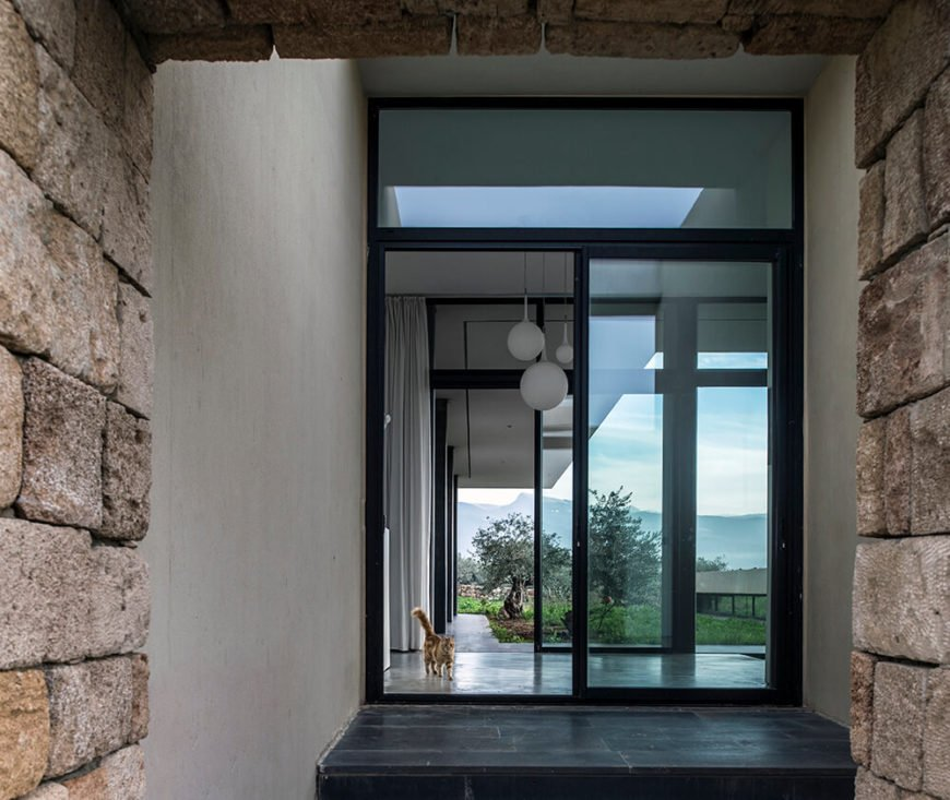 An interior view from the hall reveals the sliding doors leading out to the small yard, and you start to get a sense of how this interior design connects all spaces of the house while still having clear dividing lines.